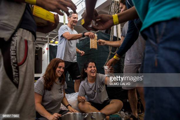 Volunteers of the ONG Proactiva Open Arms distribute food to migrants on the deck of the NGO´s boat on July 2 2018 A Spanish NGO said on June 30 2018...