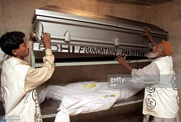 Volunteers of the private humantarian organisation, Edhi welfare trust, adjust the coffin believed to contain the remains of US journalist Daniel...