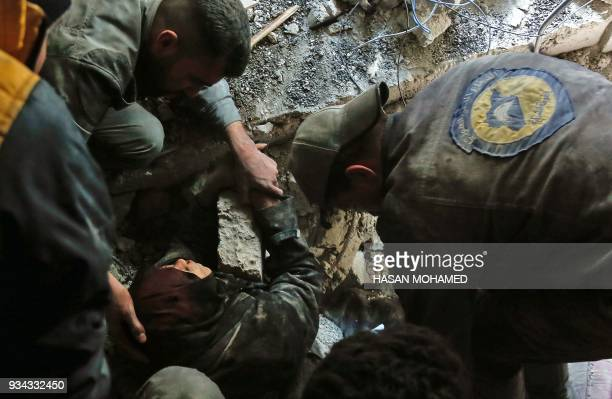 TOPSHOT Volunteers of the Syrian Civil Defense known as the White Helmets rescue a woman from the rubble of a building after an air strike in Douma...