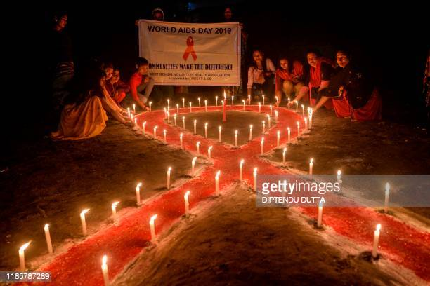 Volunteers of West Bengal Voluntary Health Association and sex workers pose for photographs as they light candles forming the shape of a red ribbon...