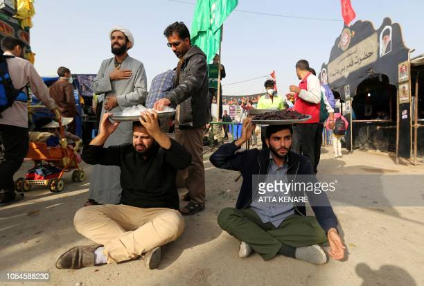 Volunteers offer food to fellow pilgrims as thousands of Iranian Shiite Muslims prepare to cross the Mehran border point between Iran and Iraq...