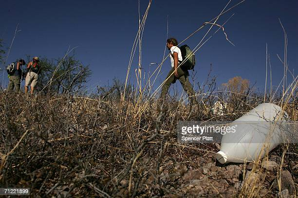 Volunteers on patrol with the humanitarian group No More Deaths pass a discarded water jug on a trail used by migrants illegally entering the US from...