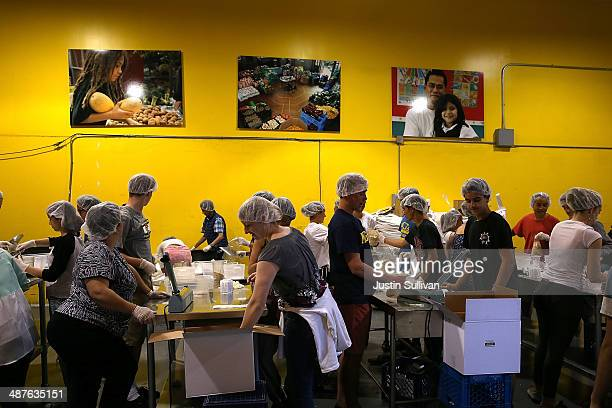 Volunteers pack bags of oatmeal at the SFMarin Food Bank on May 1 2014 in San Francisco California Food banks are bracing for higher food costs and...