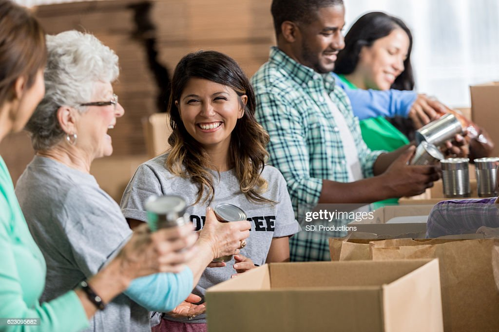 Volunteers pack canned goods into boxes during food drive : Stock Photo