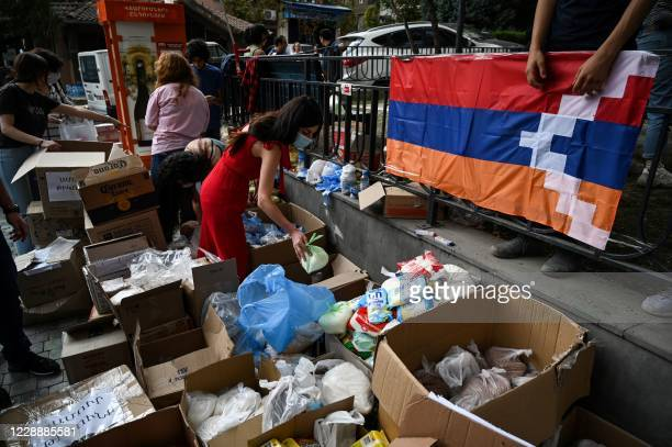 Volunteers pack food and other stuff in boxes to be sent as aid to Karabakh residents, in Yerevan on October 4 amid the ongoing fighting between...