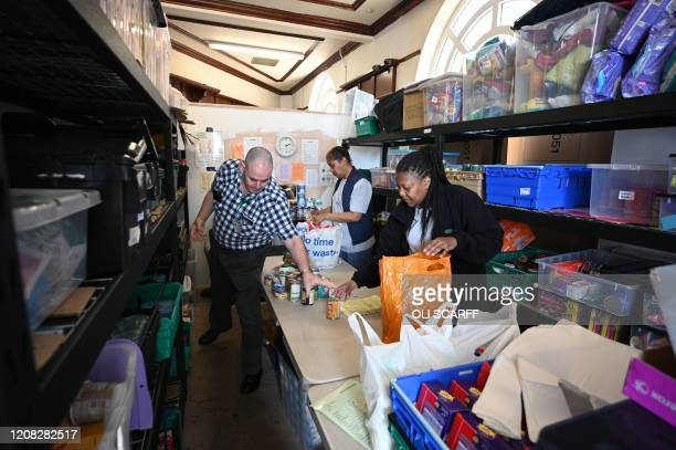 Volunteers pack food inside a Trussell Trust food bank in Oldham northwest England on March 26 2020 Panicbuying due to the coronavirus has led to...