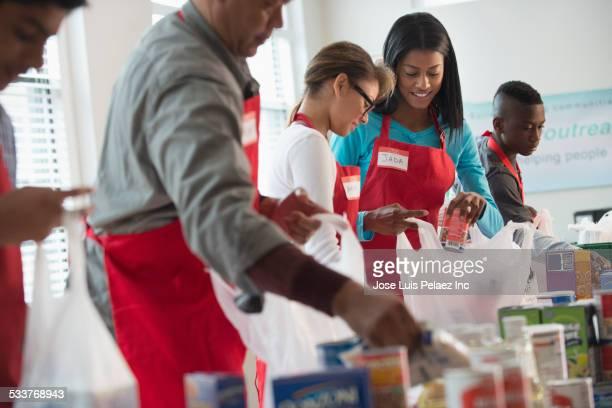 volunteers packing canned goods at food drive - matbank bildbanksfoton och bilder