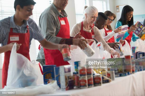 volunteers packing canned goods at food drive - charity and relief work stock pictures, royalty-free photos & images