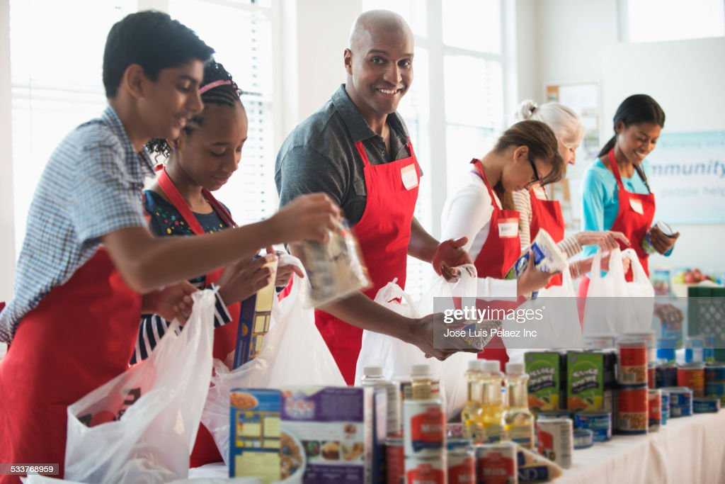 Volunteers packing canned goods at food drive : Foto stock