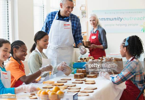 volunteers packing food in community kitchen - african american man helping elderly stock pictures, royalty-free photos & images
