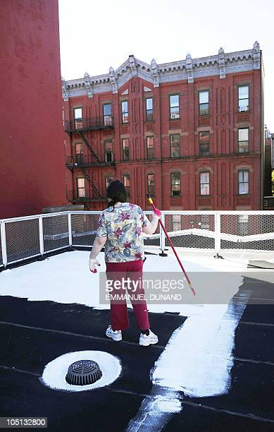 Volunteers paint a school�s roof with a special white paint that reflects nearly 80% of sunlight helping to keep the roof much cooler while reducing...
