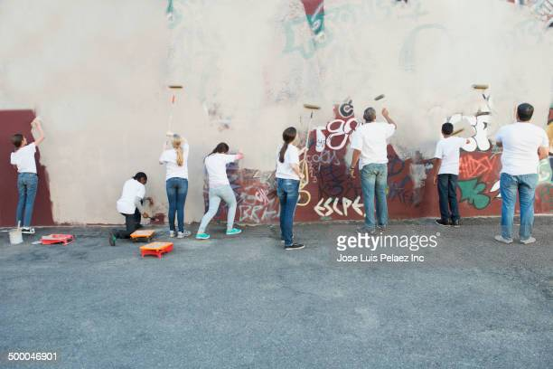 volunteers painting over graffiti wall - temas sociales fotografías e imágenes de stock