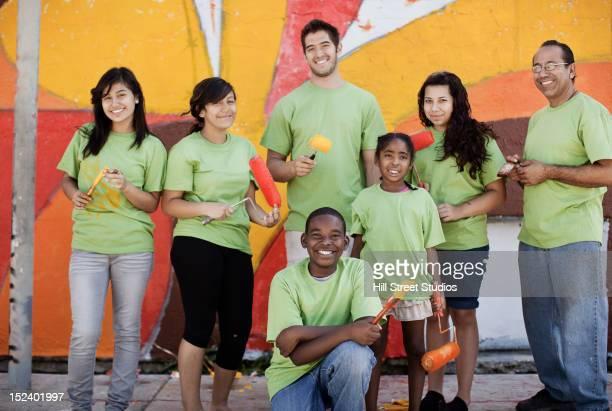 volunteers painting wall - pintar mural fotografías e imágenes de stock