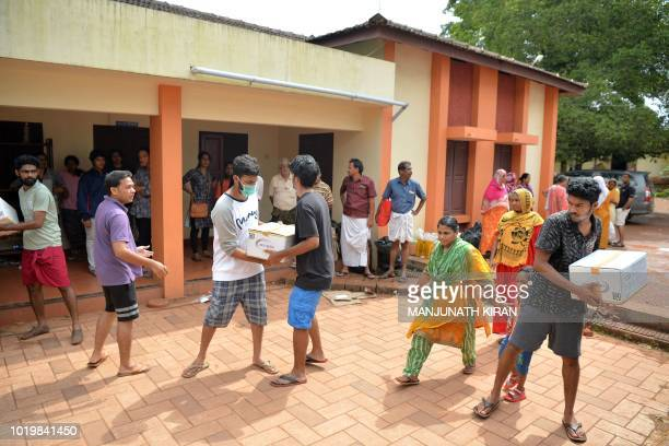 Volunteers pass boxes of food aid at a relief camp for people displaced by flooding in Aluva on the outskirts of Kochi in the south Indian state of...