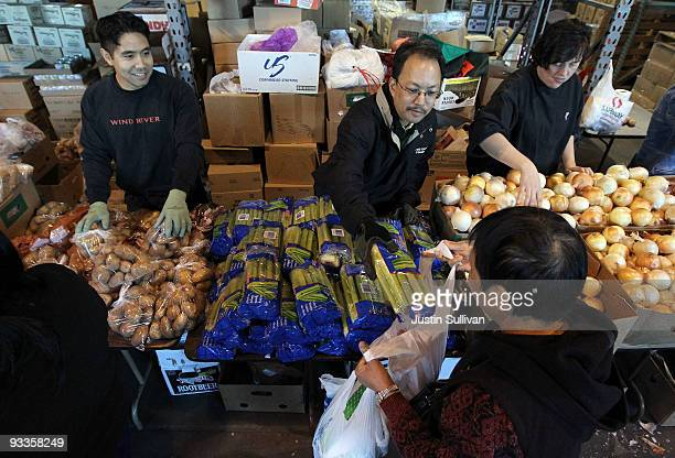 Volunteers pass out fresh vegetables for a Thanksgiving meal November 24 2009 at the Alameda Food Bank in Alameda California Hundreds of needy people...