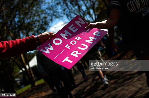 Volunteers pass out 'Women For Trump' signs before a campaign event featuring Republican presidential candidate Donald Trump at Regent University...