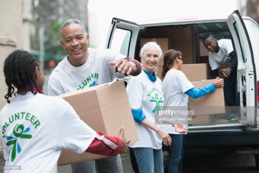 Volunteers passing cardboard boxes from delivery van : Foto stock