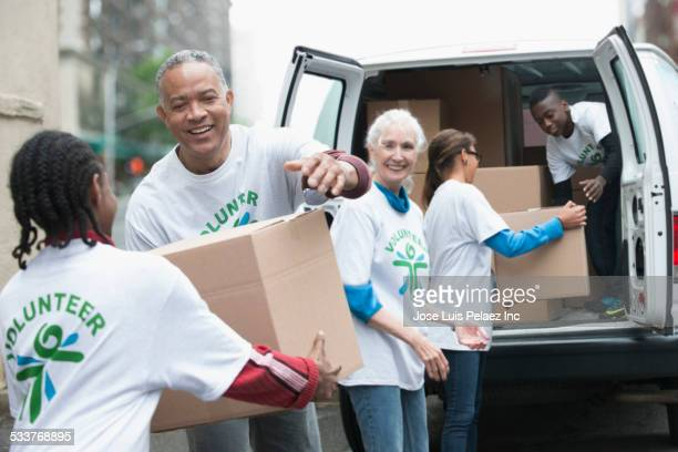 volunteers passing cardboard boxes from delivery van - volunteer stock pictures, royalty-free photos & images