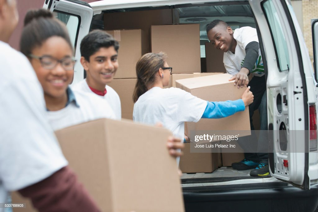 Volunteers passing cardboard boxes from delivery van : Foto stock