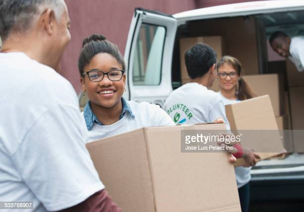Volunteers passing cardboard boxes from delivery van
