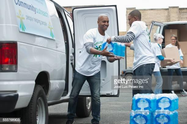 Volunteers passing stacks of bottled water from delivery van