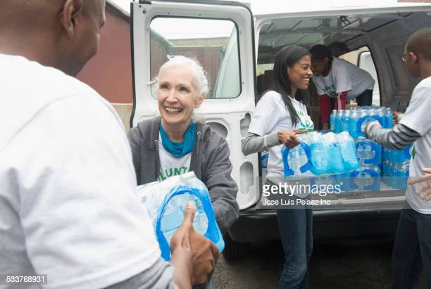 volunteers passing stacks of bottled water from delivery van - charity and relief work stock pictures, royalty-free photos & images