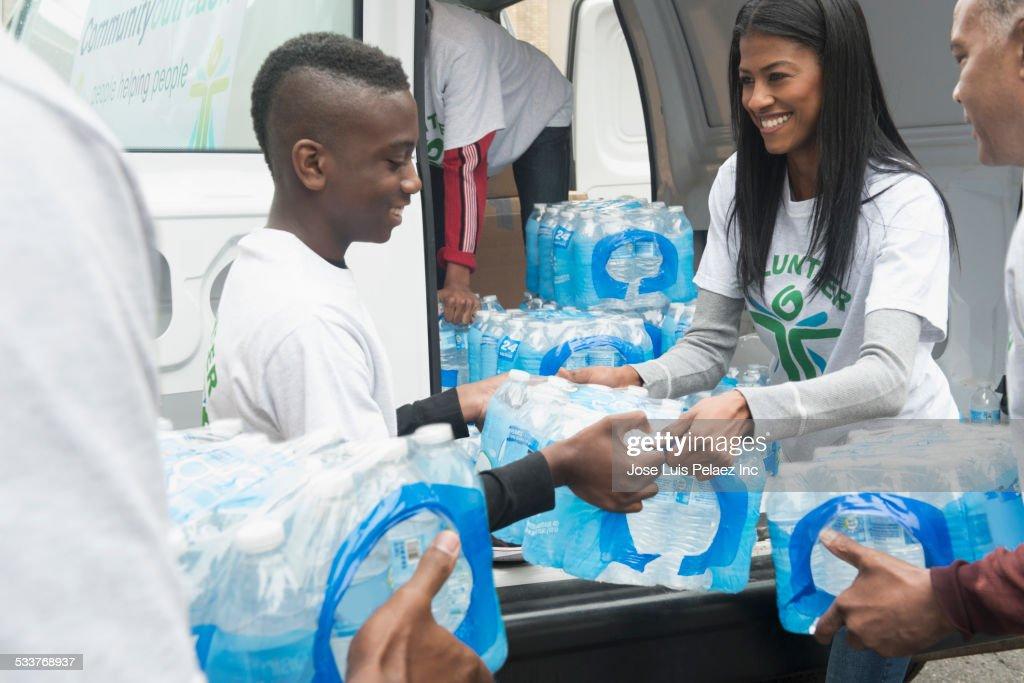 Volunteers passing stacks of bottled water from delivery van : Foto stock