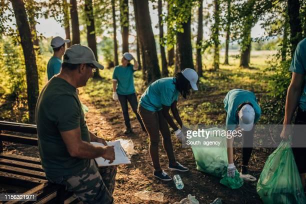 vrijwilligers plukken vuilnis op park - plukken stockfoto's en -beelden