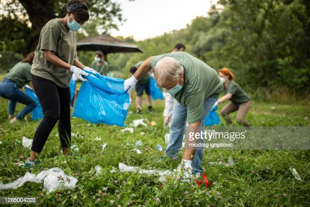 volunteers picking up garbage while cleaning public park during covid-19 pandemic - altruism stock pictures, royalty-free photos & images