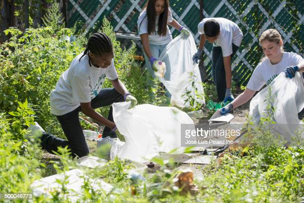 volunteers picking up litter in urban garden - city cleaning stock pictures, royalty-free photos & images