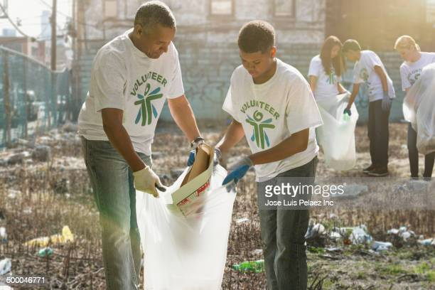 volunteers picking up litter in urban lot - city cleaning stock pictures, royalty-free photos & images
