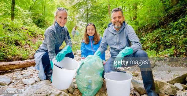 portrait smiling volunteers collecting plastic rubbish