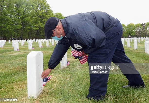Volunteers place flags at the Calverton National Cemetery on May 23 2020 in Wading River New York The US Department of Veterans Affairs suspended the...