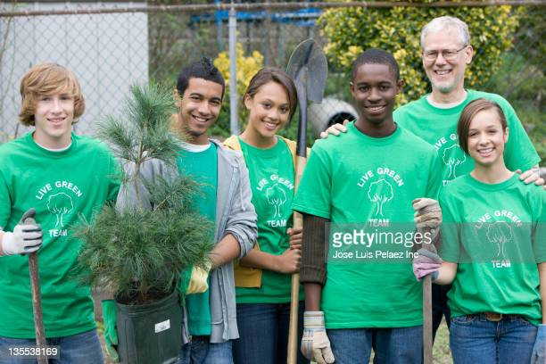 volunteers planting a tree together - african american man helping elderly stock pictures, royalty-free photos & images