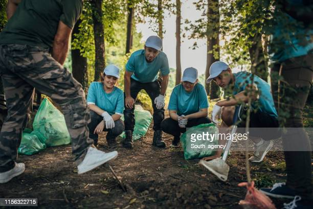 volunteers planting tree at park - ecologist stock pictures, royalty-free photos & images