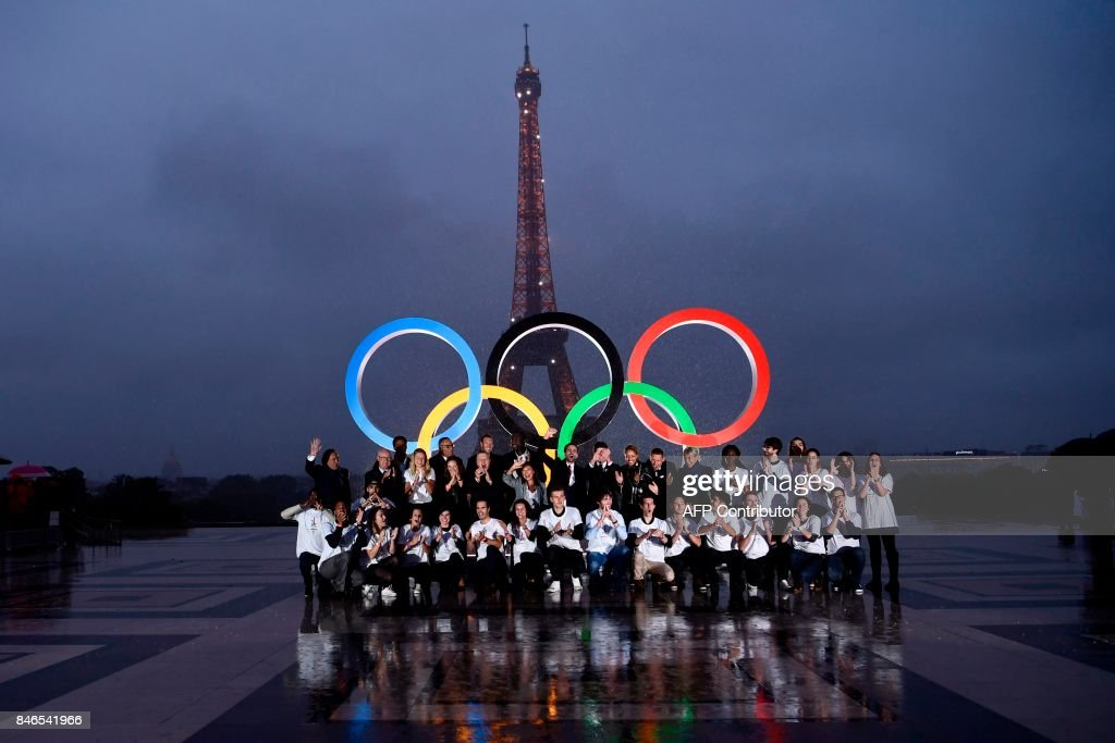 Volunteers pose in front of the Olympics Rings on the Trocadero Esplanade near the Eiffel Tower in Paris, on September 13, 2017, after the International Olympic Committee named Paris host city of the 2024 Summer Olympic Games. The International Olympic Committee named Paris and Los Angeles as hosts for the 2024 and 2028 Olympics on September 13, 2017, crowning two cities at the same time in a historic first for the embattled sports body. /