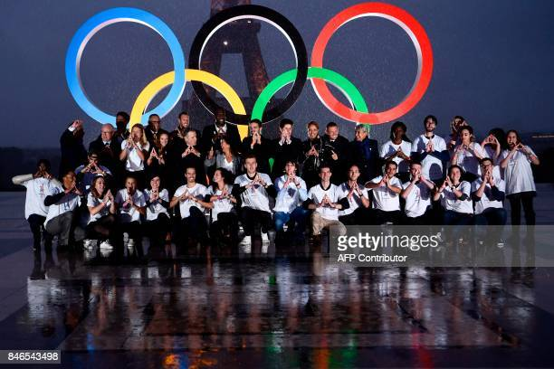 Volunteers pose in front of the Olympics Rings on the Trocadero Esplanade near the Eiffel Tower in Paris on September 13 after the International...