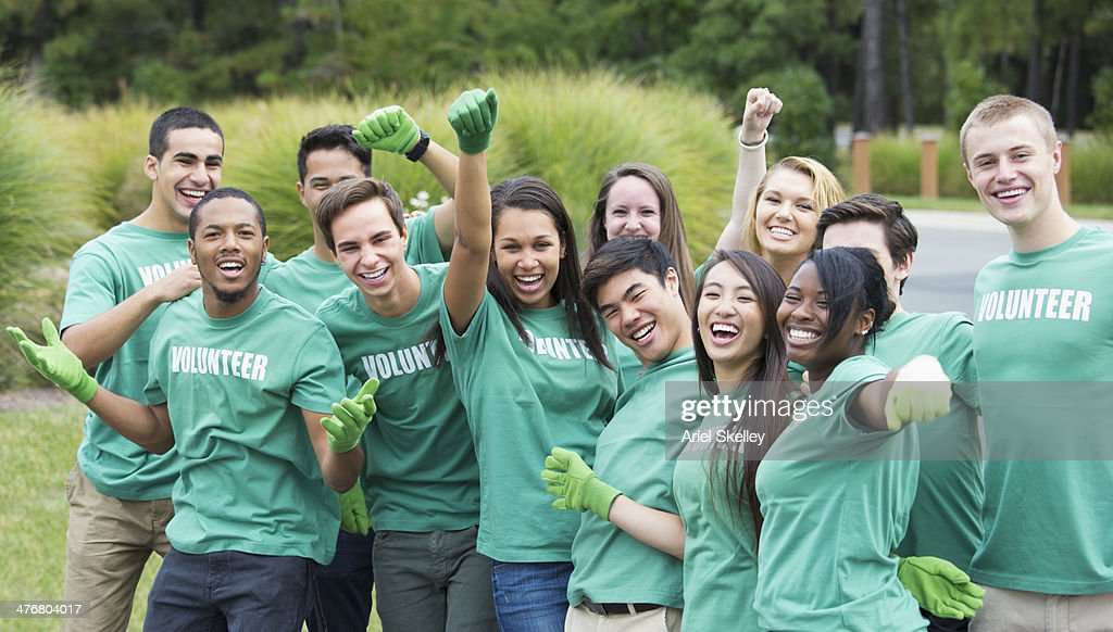 Volunteers posing together outdoors : Stock Photo