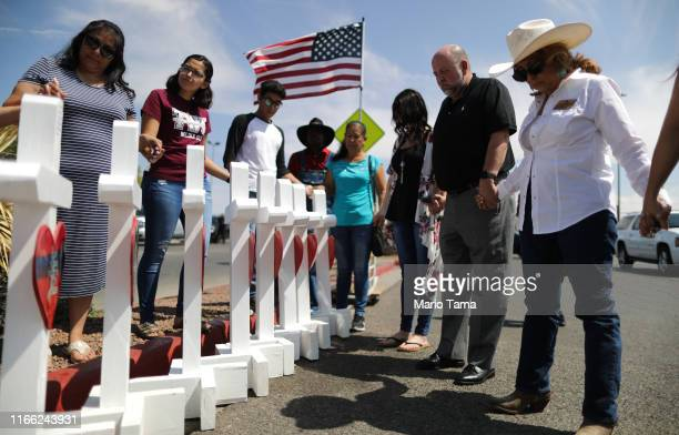 Volunteers pray over white handmade crosses memorializing the victims of a mass shooting which left at least 22 people dead on August 5 2019 in El...