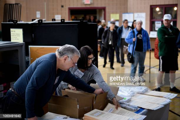 Volunteers prepare ballots as people wait to cast their ballots during early voting at a community center October 25 2018 in Potomac Maryland two...