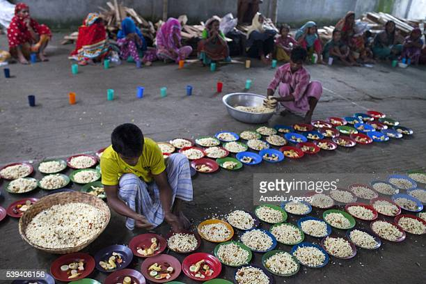 Volunteers prepare fastbreaking dinner as homeless people wait during the Islamic holy month of Ramadan at the High Court of Mazar in Dhaka...