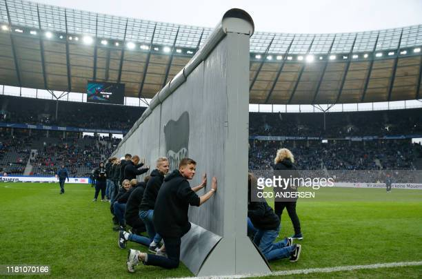 "Volunteers prepare to knock over mock-up of the former Berlin Wall bearing the inscrition ""Against Walls together with Berlin"" standing across the..."