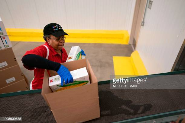 Volunteers prepare to pack boxes of food to be distributed to those in need at the Capital Area Food Bank on April 1 2020 in Washington DC The...