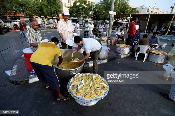 Volunteers prepares food for Iftar the evening meal to break fast during the holy month of Ramadan on June 22 2016 in Dubai United Arab Emirates...