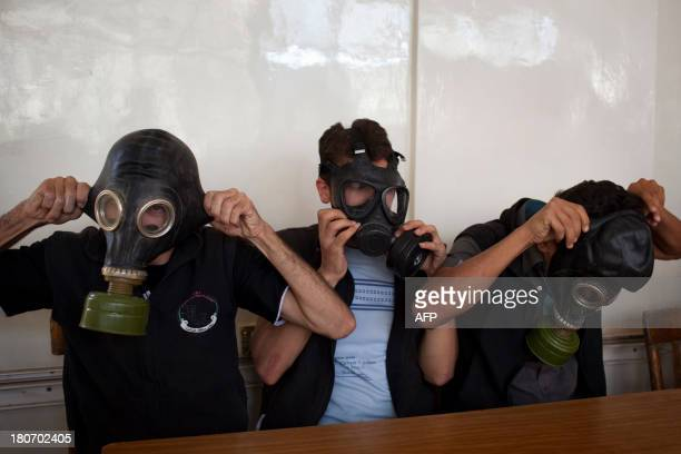 Volunteers put on gas masks during a class on how to respond to a chemical attack in the northern Syrian city of Aleppo on September 15 2013 For two...