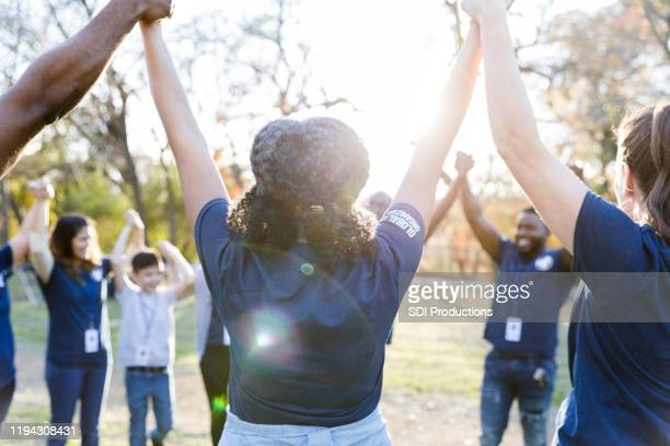 volunteers raise hands in unity during - non profit organization stock pictures, royalty-free photos & images