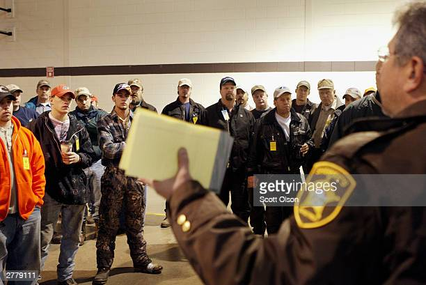 Volunteers receive instructions from a Polk County deputy sheriff at the National Guard armory in Crookston Minnesota December 3 2003 before...