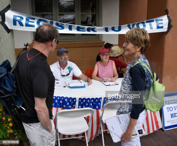 Volunteers register voters at a table set up at a Fourth of July holiday event in Santa Fe New Mexico
