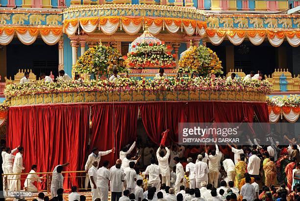 Volunteers remove curtains after the final rituals of the burial of Hindu guru Sathya Sai Baba inside Prashanthi Nilayam in the village of...
