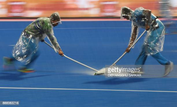 TOPSHOT Volunteers remove rain water from the ground prior to the start of the semifinals of the Hockey World League Final match between India and...